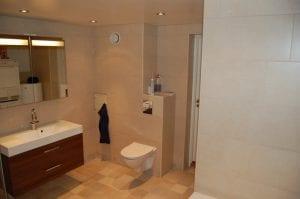 nytt baderom med lyse fliser, innebygd sisterne , baderomsinnredning og spotlights